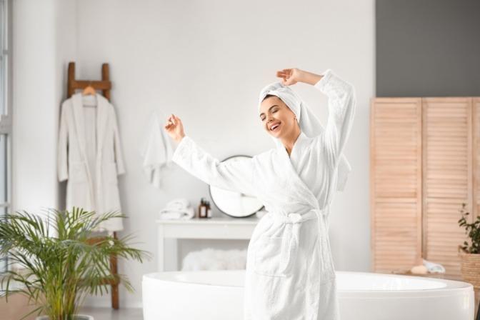 Eine Frau war kalt duschen und tanzt in guter Stimmung im Bad