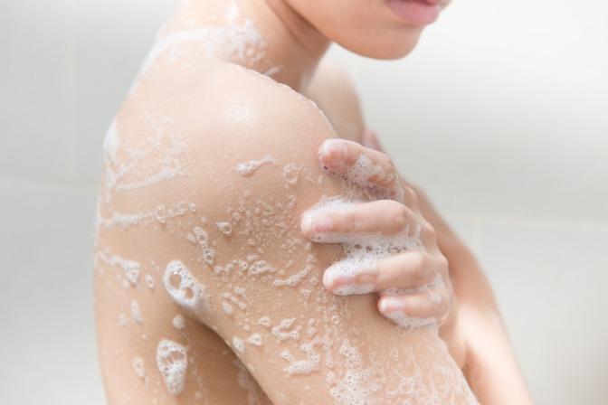 Eine Frau seift ihre Haut unter der kalten Dusche ein