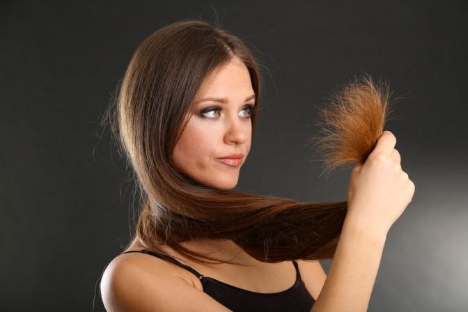 Frau mit langen kaputten Haaren vor dem Reparieren