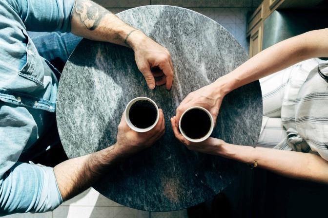 Zwei Menschen sitzen mit Kaffee am Tisch.