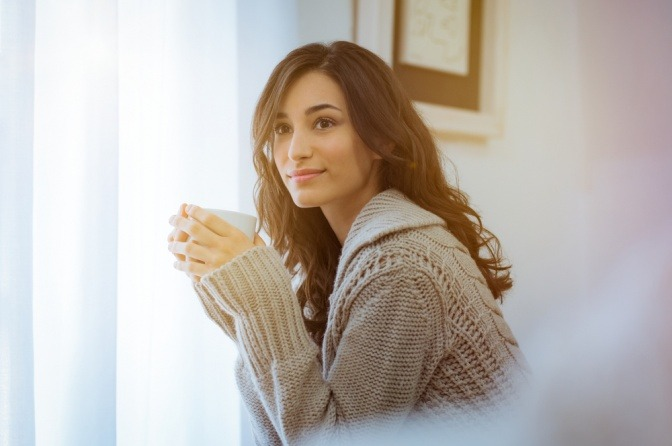 Eine Frau trinkt als Hautpflege von innen