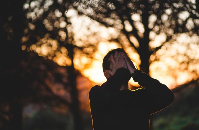Ein Mann steht im Wald und hält sich die Hände vor das Gesicht.
