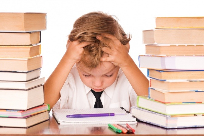 Ein Kind sitzt verzweifelt zwischen ein paar Büchern
