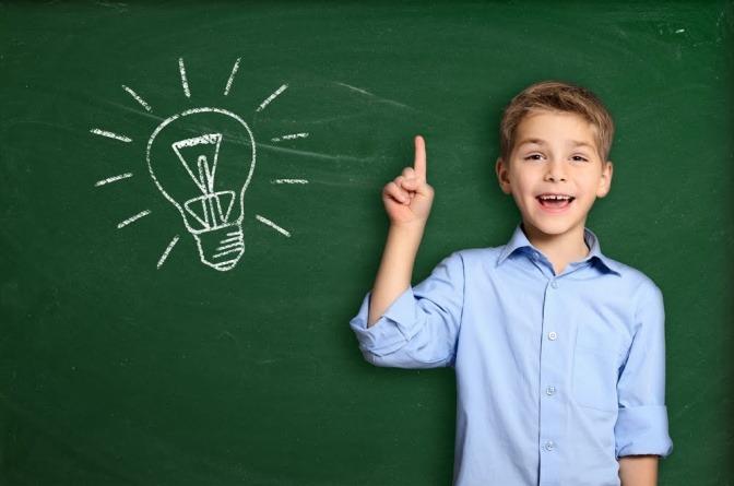 Junge vor Tafel mit aufgezeichneter Glühbirne.