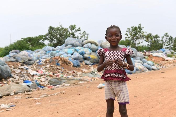 Kind steht vor einem Müllberg