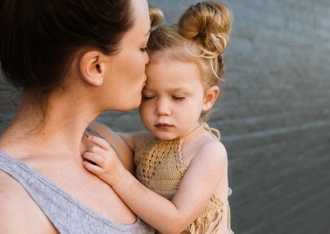 Eine Mutter küsst ihr Kind