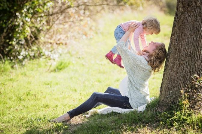 Eine Frau hebt glücklich ihr Kind in die Höhe