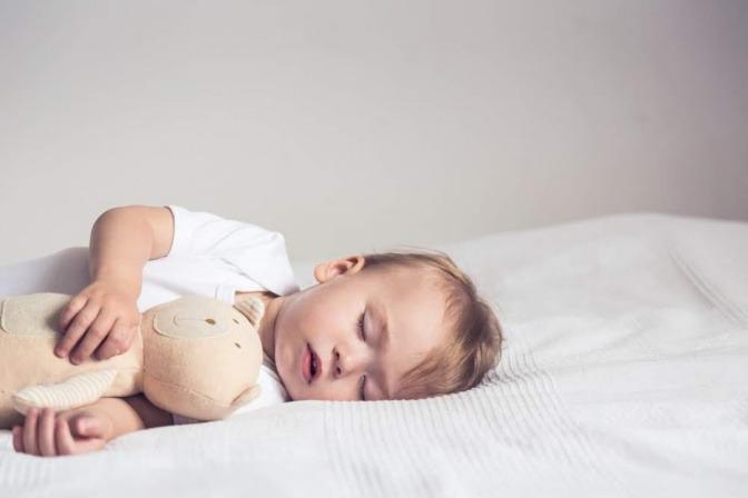 Ein Kind schläft mit einem Kuscheltier