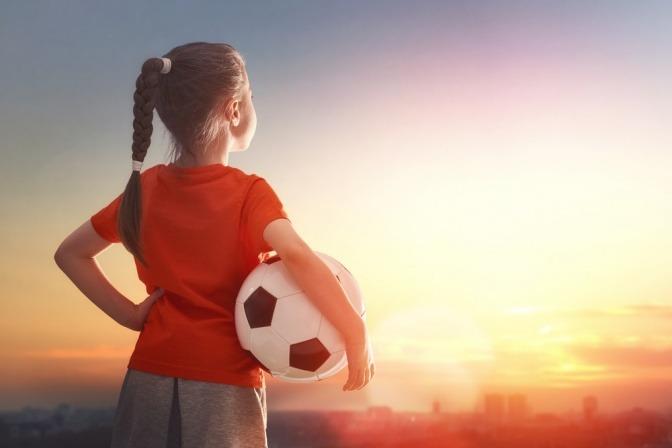 Ein kleines Mädchen mit einem Fußball unter dem Arm träumt davon, ein Sportstar zu werden.