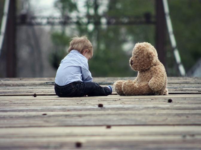 Ein Kind sitzt neben einem Teddybär