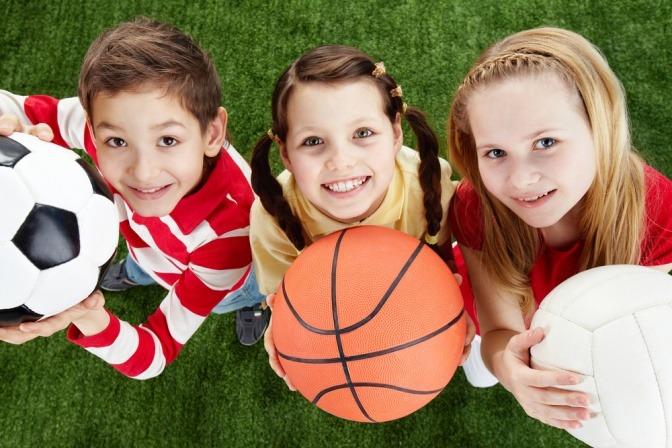 Drei kleine Kinder mit unterschiedlichen Sportbällen im Arm blicken in freudiger Erwartung einer anstehenden Spielstunde hoch zu ihren Eltern.