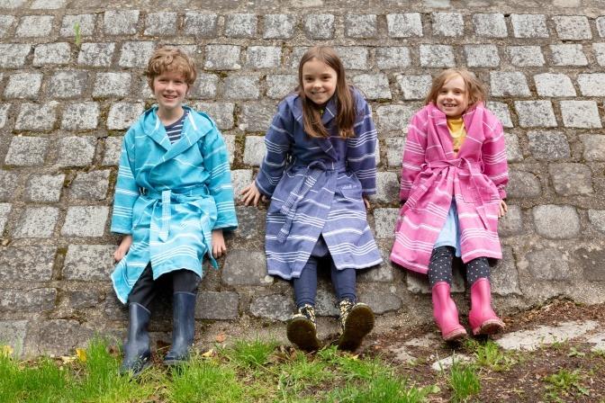 drei Kinder in bunten Bademänteln