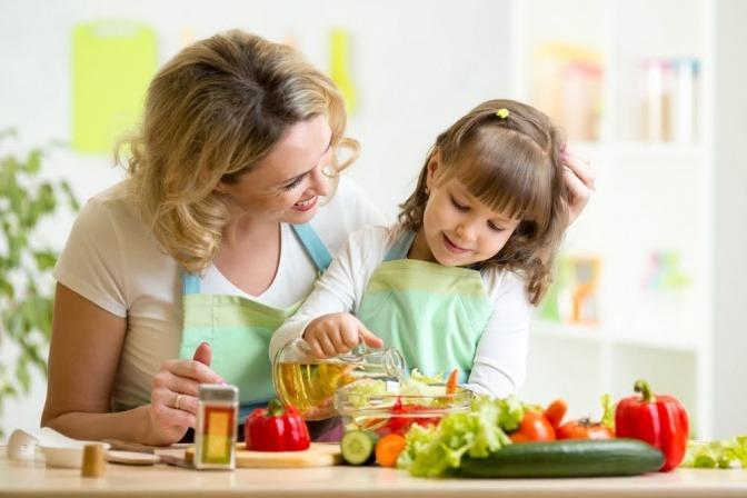 Frau mit Kind beim Kochen.