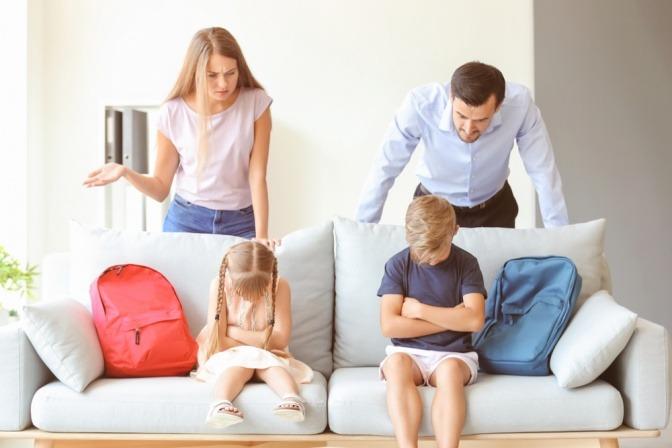 Eltern maßregeln und beschämen ihre Kinder nach einem vermeintlichen Fehlverhalten in der Schule.