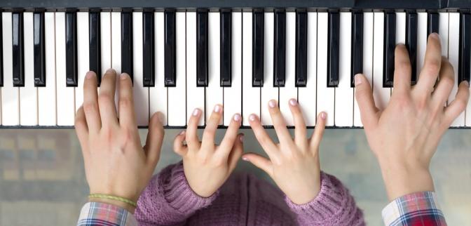 Klaviertasten mit zwei Händen die darauf spielen