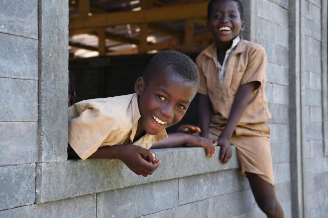 Kinder schauen aus einem Klassenzimmer aus Plastik