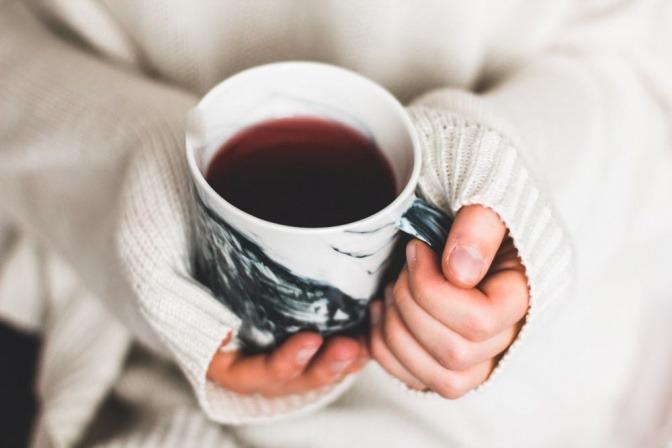 Frau hält Teetasse zum Körper entwässern
