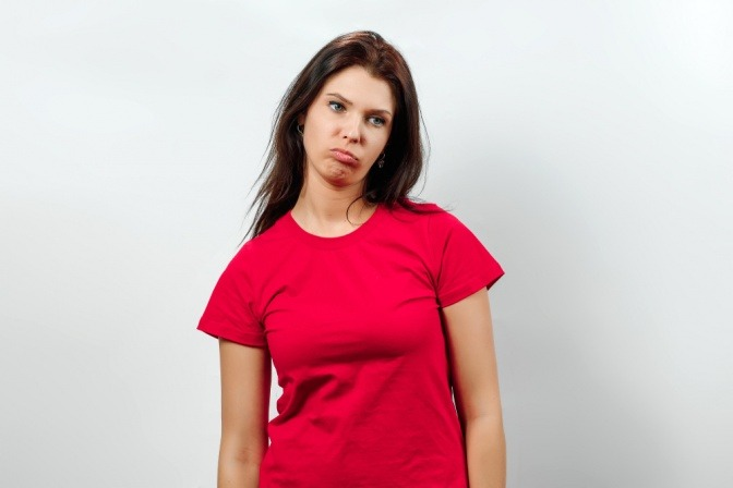 Junge Frau in rotem T-Shirt blickt zerknirscht und angesäuert drein.
