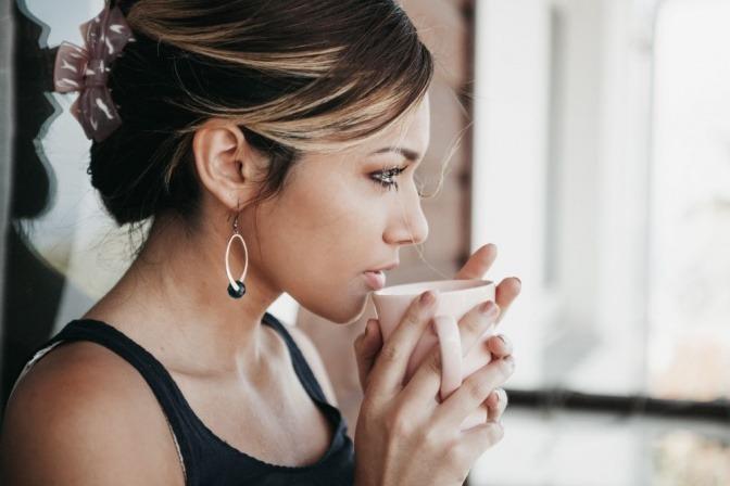 Eine Frau trinkt Kaffee, in dem Koffein enthalten ist