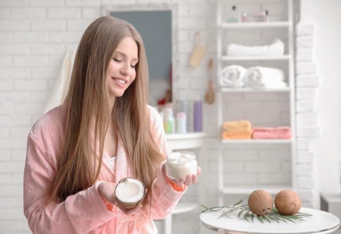 Frau im Badezimmer mit Kokosöl für die Haare in der Hand