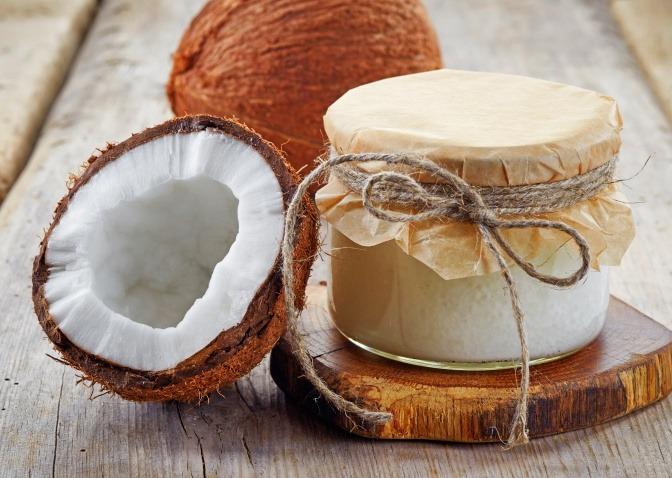 Kokosnüsse und Glas mit Kokosöl