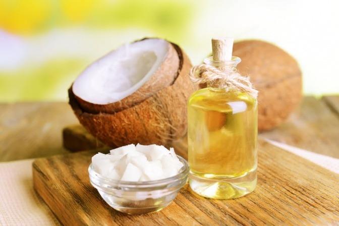 Kokosöl in einer Flasche, daneben eine Kokosnuss