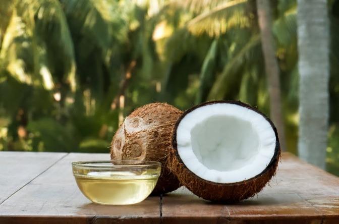 Eine Kokosnuss ist aufgeschnitten und Kokosöl steht daneben