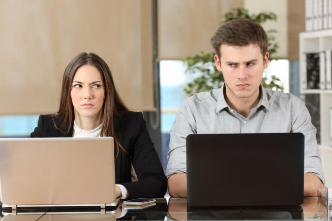 Zwei Kollegen sitzen nebeneinander mit bösen Blicken