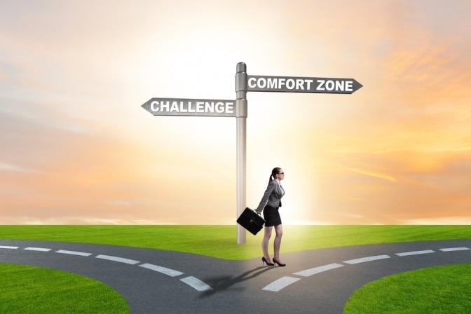 Frau steht vor Weggabelung, links geht es zu einer Herausforderung, nach rechts zeigt ein Pfeil zur Komfortzone.