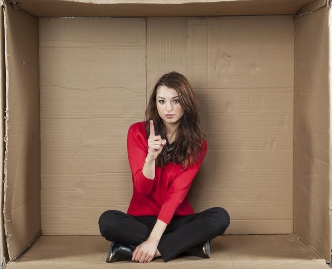 Eine selbstbewusste junge Frau sitzt in einer Box aus Karton und erhebt mahnend den Zeigefinger.