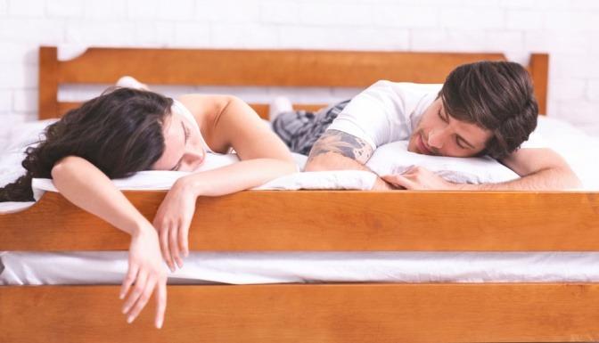 Mann und Frau liegen im Bett und wirken sehr gelangweilt und demotiviert.