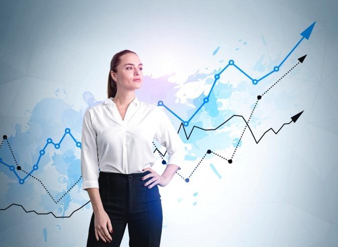 Frau in Business-Anzug mit zuversichtlichem Blick, Hand auf Taille, steigende blaue und schwarze Pfeile auf blauem bunten Hintergrund.