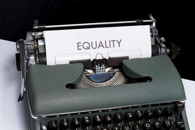 Eine alte Schreibmaschine, in die ein Blatt Papier mit der Aufschrift EQUALITY eingespannt ist.