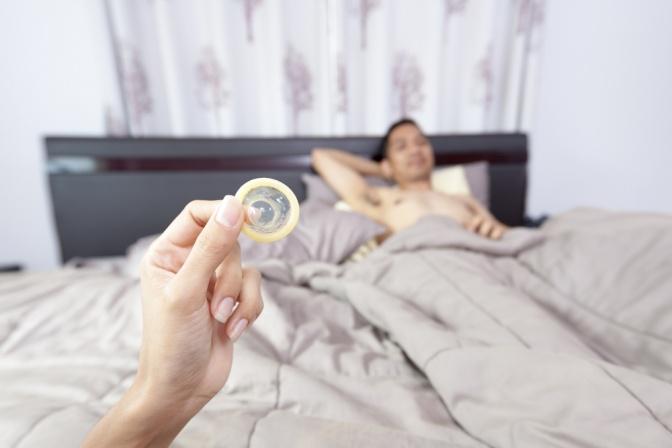 Eine Frau zeigt einem Mann im Bett ein Kondom