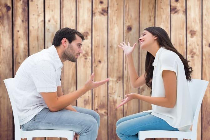 Paar sitzt einander gegenüber und diskutiert.