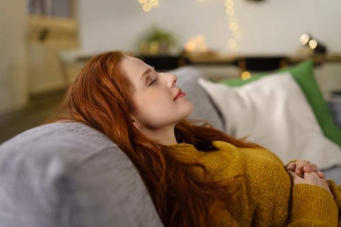 Eine junge rothaarige Frau liegt mit geschlossenen Augen auf einem Sofa und praktiziert Achtsamkeitsmeditation.