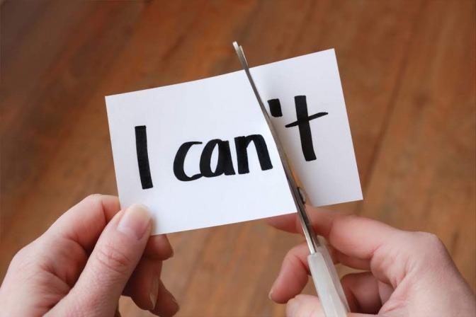 Ein Zettel auf dem I can't steht. Eine Hand hält eine Schere und schneidet den hinteren Teil ab, sodass aus der Nachricht I can wird.