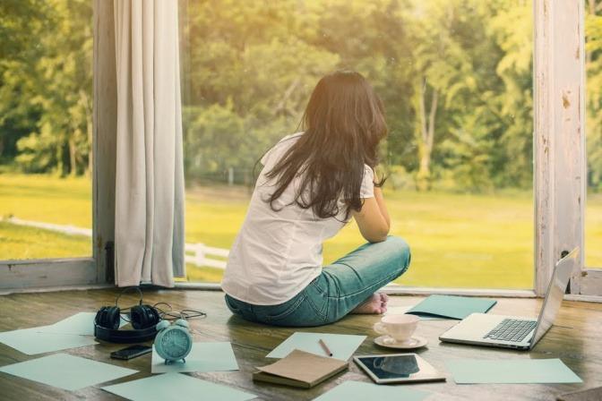 Eine Frau sitzt im Schneidersitz in einer Art Wintergarten und blickt durch die Fenster ins Grüne. Um sie herum liegen diverse Arbeitsmaterialien wie Schreibblock, Tablet, Stifte und mehr.