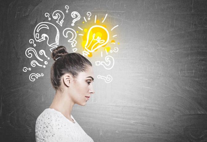 Die Seitenansicht einer an einem Tisch sitzenden Frau. Über ihrem Kopf sind einige Muster und Symbole in die Luft gezeichnet. Eine leuchtende Glühbirne steht für das Thema Konzentration steigern.