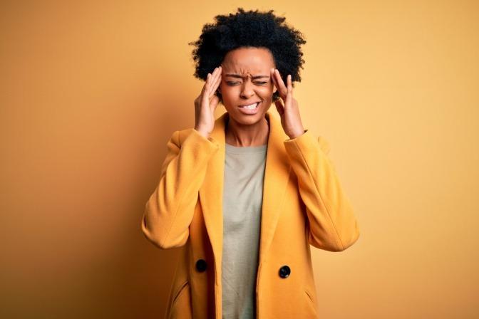 Eine Frau hält den Kopf wegen Kopfschmerzen oder Migräne