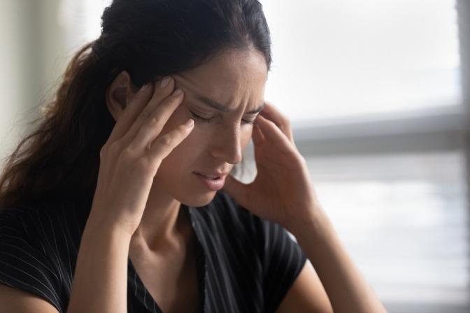 Eine Frau hat Migräne oder Kopfschmerzen