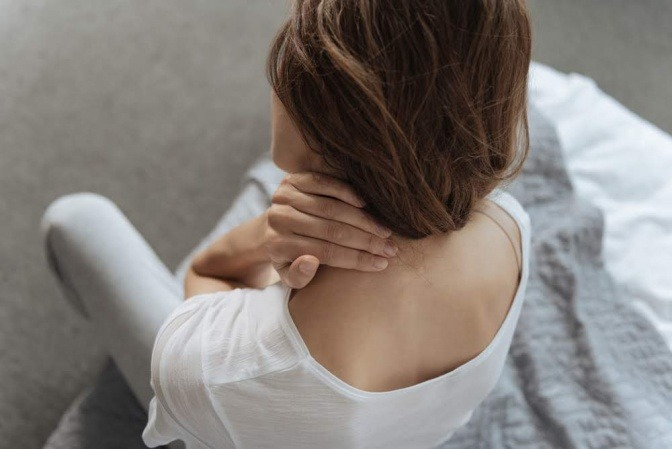 Frau massiert sich den Nacken
