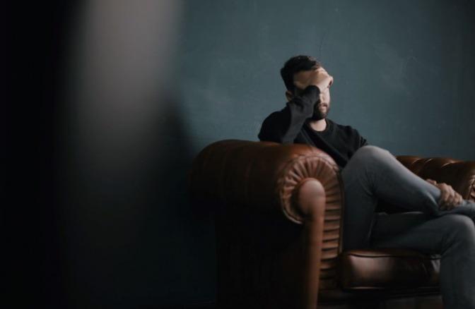 Ein Mann in seiner Lebensmitte sitzt mit einer Krise auf einem Sofa
