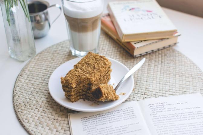 Neben einem Kuchen steht eine Tasse Kaffee