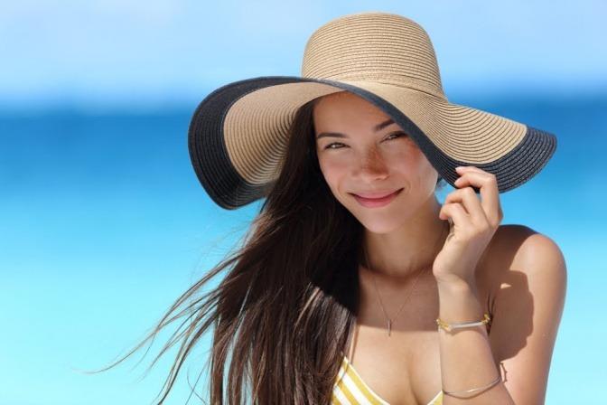Frau mit Sonnenhut will kühlen Kopf bewahren