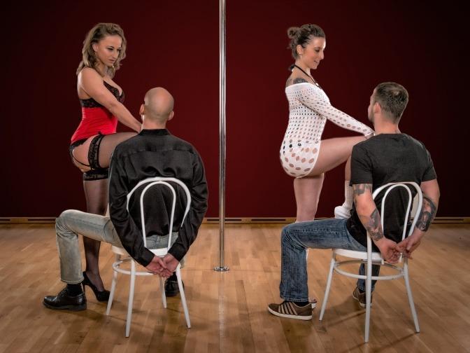 Zwei Frauen tanzen für zwei Männer einen Lapdance