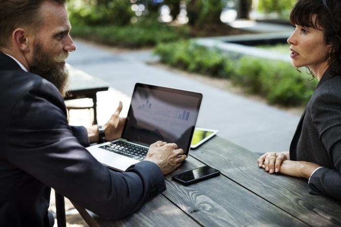 Ein Mann sitzt beim Laptop, eine Frau gegenüber