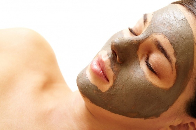 Eine Frau hat eine Maske aus Lavaerde im Gesicht