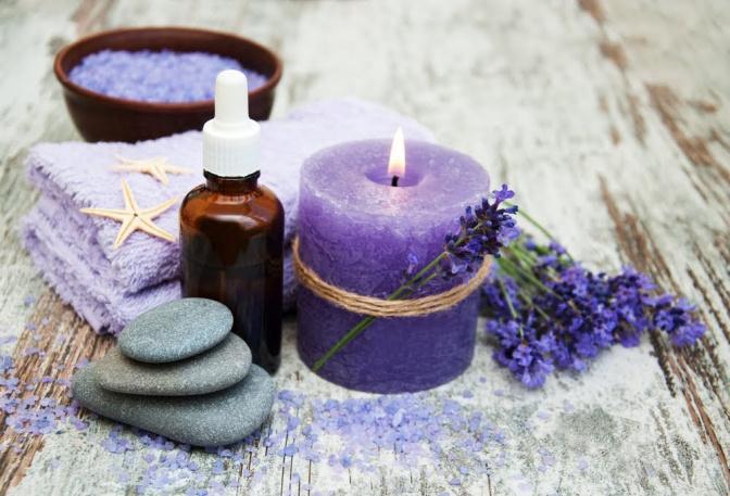 Einige Zweige einer Lavendelpflanze sind neben einer kleinen Glasflasche, einigen dekorativen Steinen und einem Turm aus Waschlappen drapiert.