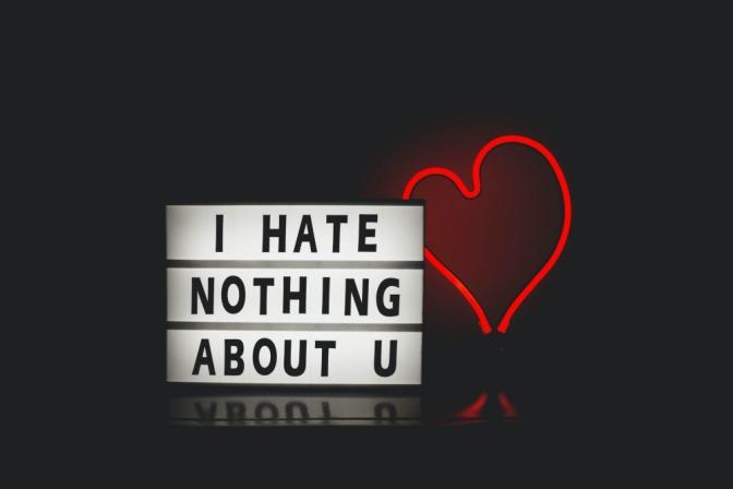 """Der Schriftzug """"I hate nothing about you"""" neben einem leuchtenden roten Herz aus Neonröhren."""